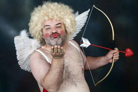 Photo for Fat bearded mature hairy cupid with bow and heart arrow. Sending a kiss - Royalty Free Image