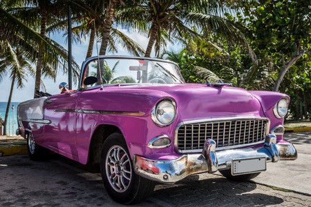 Photo pour Pink cabriolet classic car parked on the beach in Cuba - image libre de droit