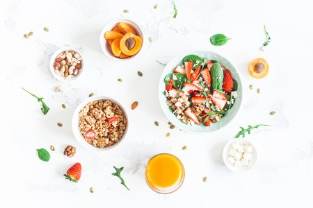 Photo for Breakfast with muesli, strawberry salad, fresh fruit, orange juice, nuts on white background. Healthy food concept. Flat lay, top view - Royalty Free Image