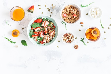 Photo pour Breakfast with muesli, strawberry salad, fresh fruit, nuts on white background. Healthy food concept. Flat lay, top view - image libre de droit