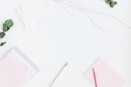 Photo pour Feminine workspace with notebook, paper blank, decorative branch, pencils. Business concept. Flat lay, top view - image libre de droit