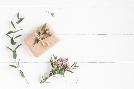 Photo pour Flowers composition. Gift, pink flowers and eucalyptus branches on white wooden background. Flat lay, top view - image libre de droit