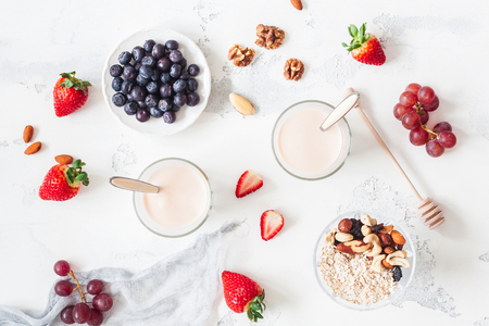 Foto de Breakfast with muesli, yogurt, strawberry, blueberry, nuts on white background. Healthy food concept. Flat lay, top view - Imagen libre de derechos
