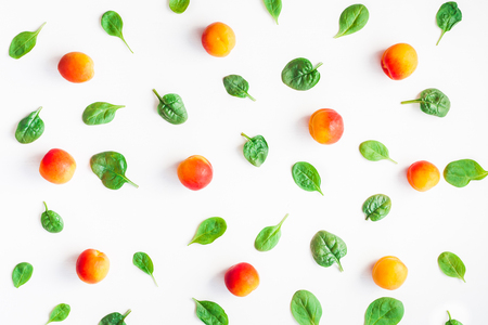 Foto de Apricot and spinach leaves on white background. Fruit pattern. Top view, flat lay - Imagen libre de derechos