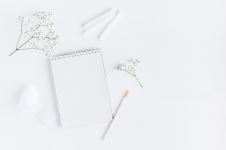 Foto de Workspace with notebook, paper blank, gypsophila flowers, pencils. Wedding concept. Flat lay, top view - Imagen libre de derechos