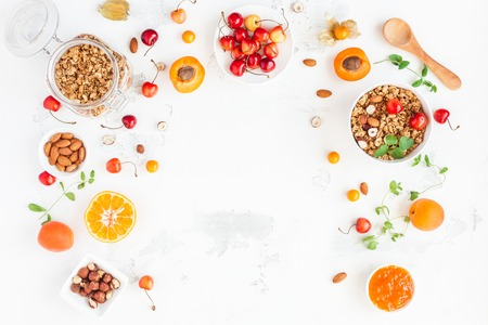 Foto de Breakfast with muesli, fruits, berries, nuts on white background. Healthy food concept. Flat lay, top view, copy space - Imagen libre de derechos