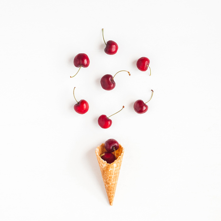 Photo pour Cherry in waffle cone on white background. Creative food concept. Flat lay, top view, square - image libre de droit