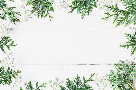 Foto de Christmas frame made of thuja branches and gypsophila flowers on white wooden background. Christmas, winter, new year concept. Flat lay, top view, copy space - Imagen libre de derechos