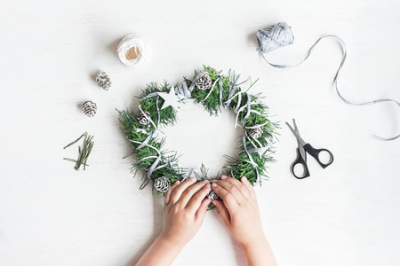 Foto de Christmas. Child making handmade christmas wreath. Top view, flat lay - Imagen libre de derechos
