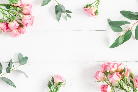 Photo pour Flowers composition. Frame made of eucalyptus branches and pink rose flowers on white wooden background. Flat lay, top view, copy space - image libre de droit