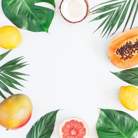 Foto de Summer tropical composition. Green palm leaves and tropical fruits on gray background. Summer concept. Flat lay, top view, copy space - Imagen libre de derechos