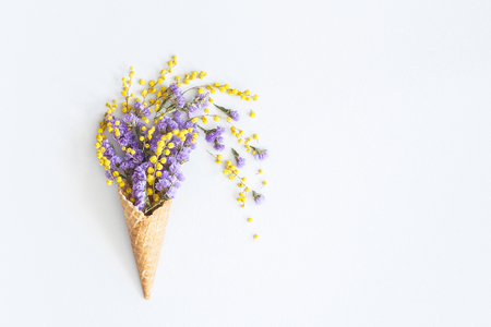 Photo pour Flowers composition. Purple and yellow flowers in waffle cone. Flat lay, top view, copy space - image libre de droit