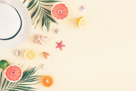 Photo pour Summer composition. Fruits, hat, tropical palm leaves, seashells on pastel yellow background. Summer concept. Flat lay, top view, copy space - image libre de droit