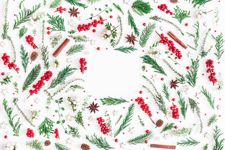 Photo pour Christmas composition. Frame made of christmas tree branches, red berries, cinnamon sticks, anise stars, decorations on white background. Flat lay, top view, copy space - image libre de droit
