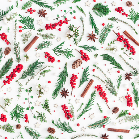 Photo pour Christmas composition. Pattern made of christmas tree branches, red berries, cinnamon sticks, anise stars, decorations on white background. Flat lay, top view, square - image libre de droit