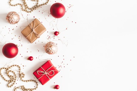Foto de Christmas composition. Christmas gifts, red and golden decorations on white background. Flat lay, top view, copy space - Imagen libre de derechos