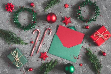 Foto de Christmas composition. Gifts, fir tree branches, envelope, card, red decorations on black background. Christmas, winter, new year concept. Flat lay, top view - Imagen libre de derechos
