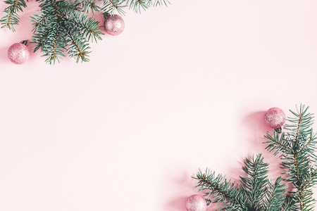 Photo pour Christmas composition. Frame made of fir tree branches, pink balls on pastel pink background. Christmas, winter, new year concept. Flat lay, top view, copy space - image libre de droit
