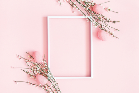 Photo for Easter composition. Easter eggs, photo frame, white flowers on pastel pink background. Flat lay, top view, copy space - Royalty Free Image