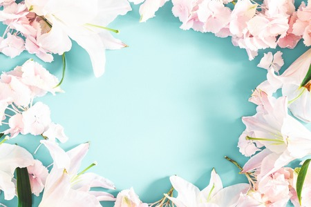 Foto de Flowers composition. Pattern made of pink and white flowers on pastel blue background. Flat lay, top view - Imagen libre de derechos