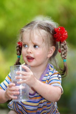 Littlel girl drinking glass of water. Outdoor.