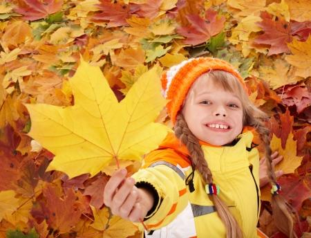 Little girl in autumn orange leaves. Outdoor.