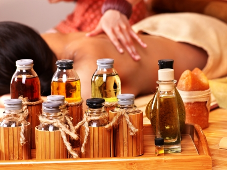 Young woman getting massage in bamboo spa.