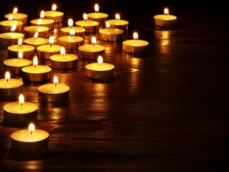 Photo pour Group of burning candles on  black background. - image libre de droit
