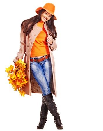 Woman wearing overcoat holding  orange leaves.