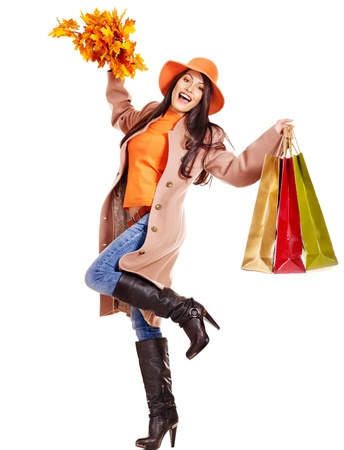 Woman wearing autumn overcoat and hat holding shopping bag.