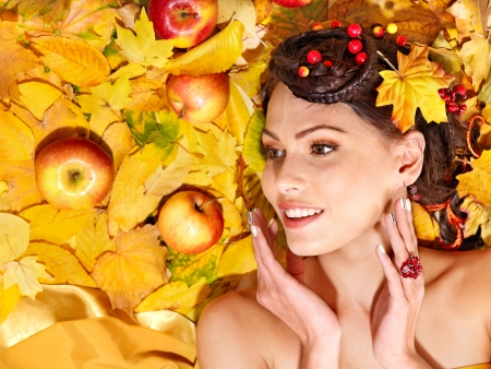 Woman holding autumn apple and leaves.