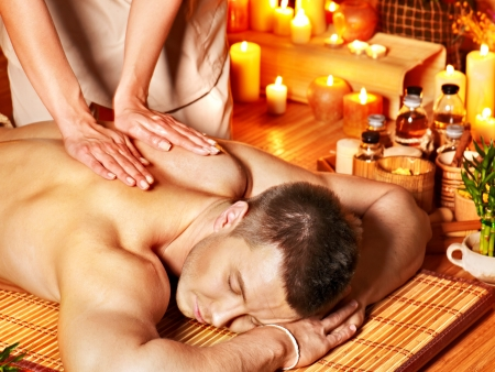Foto de Man getting aroma massage in bamboo spa. - Imagen libre de derechos