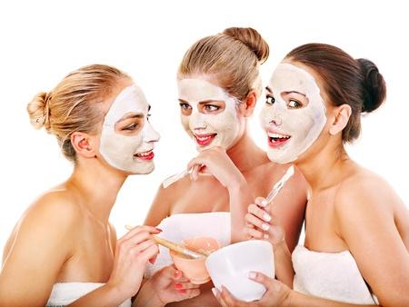 Foto de Young woman getting facial mask and gossip . Isolated. - Imagen libre de derechos