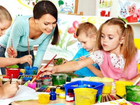 Foto de Happy children  with teacher painting. - Imagen libre de derechos