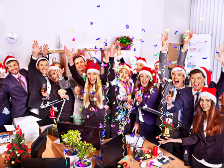 Foto de Happy group people in santa hat at Xmas business  party. - Imagen libre de derechos