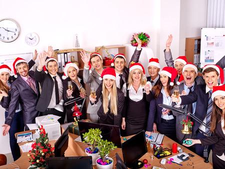 Foto de Happy group people in santa hat at Xmas business  party. - Imagen libre de derechos