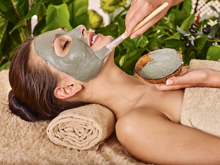 Photo pour Woman with clay facial mask in beauty spa. In background tropical plants - image libre de droit