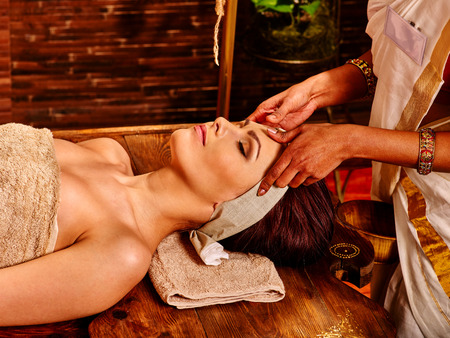 Photo pour Woman having facial  ayurveda spa treatment. Wooden brown bed - image libre de droit