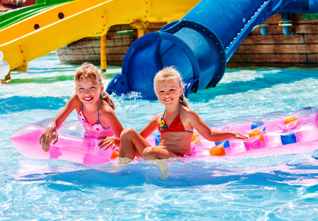 Photo for Kids are floating on inflatable mattress in water park. Summer holiday. - Royalty Free Image