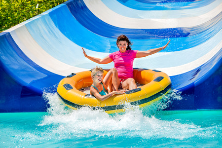 Photo for Child with mother on water slide at aquapark. Two persons on summer holiday. - Royalty Free Image