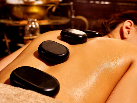 Foto de Young woman having Ayurveda stone massage. - Imagen libre de derechos