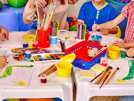 Foto de Group kids hands holding colored paper and glue on table in kindergarten . - Imagen libre de derechos