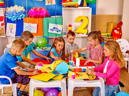 Foto de Group kids learning and holding colored paper and glue on table in kindergarten . - Imagen libre de derechos