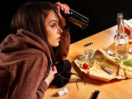 Foto de Drunk girl holding bottle of alcohol. Soccial issue alcoholism. Side view. - Imagen libre de derechos