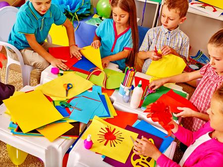 Foto de Large Group kids holding colored paper on table in kindergarten . - Imagen libre de derechos