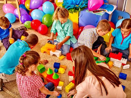 Foto de Group children game blocks and balloons on floor in kindergarten . Top view. - Imagen libre de derechos