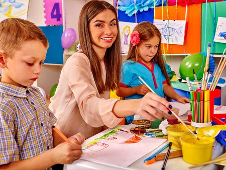 Foto de Children with female teacher painting on paper by paint and pencils  in  kindergarten . - Imagen libre de derechos
