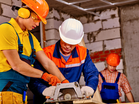 Photo for Working group people builder with circular saw. Brick wall in background. - Royalty Free Image