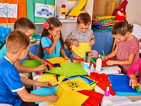 Photo pour Child cutting paper in class. Kids development and social lerning children in school. Childrens project in kindergarten. Pictures into background. - image libre de droit