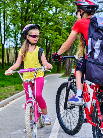 Bicycle path and sign with children. Girls wearing bicycle helmet with rucksack ciclyng ride. Kids are on white bike lane. Alternative to urban transport. Oncoming traffic. Unexpected meeting of two girlfriends.